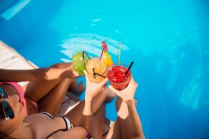Ladies holding tropical drinks - Retreat Pool & Cabanas